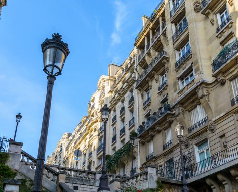 Low angle view of opulent-looking, Haussmannian style buildings in the chic neighborhoods of Paris, with period street lights in the foreground against blue sky.